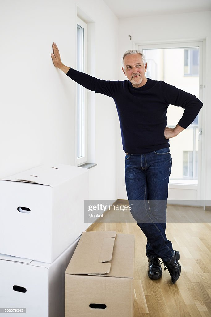 Full length of mature man standing by moving boxes at home : Stock Photo