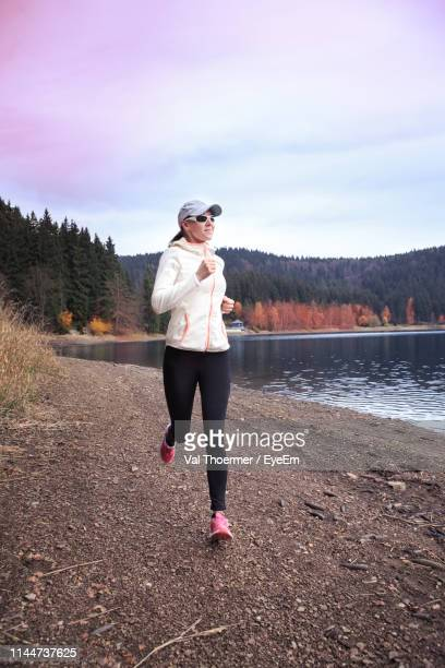 full length of mature woman running on field against sky in forest during sunset - val thoermer stock-fotos und bilder