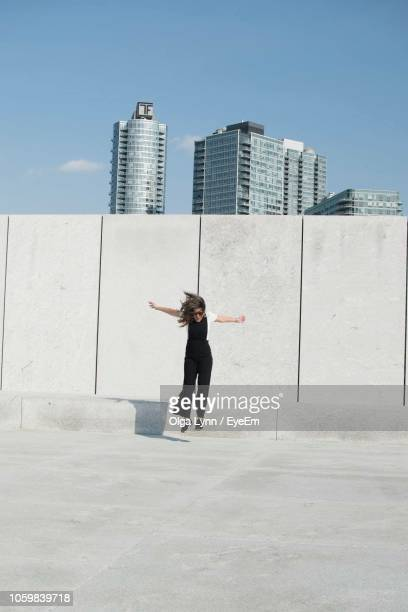 full length of mature woman with arms outstretched jumping against wall during sunny day - lynn pleasant stock pictures, royalty-free photos & images