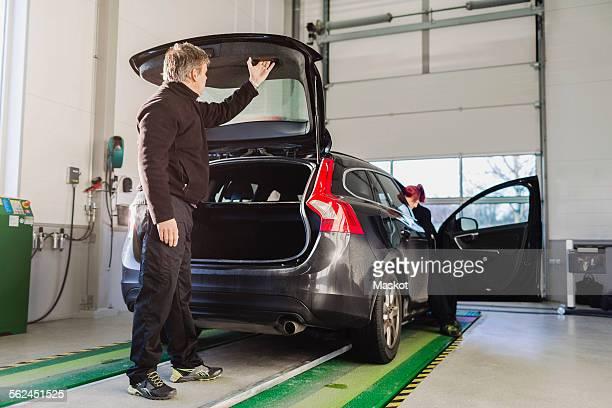 Full length of mechanic closing car trunk in auto repair shop