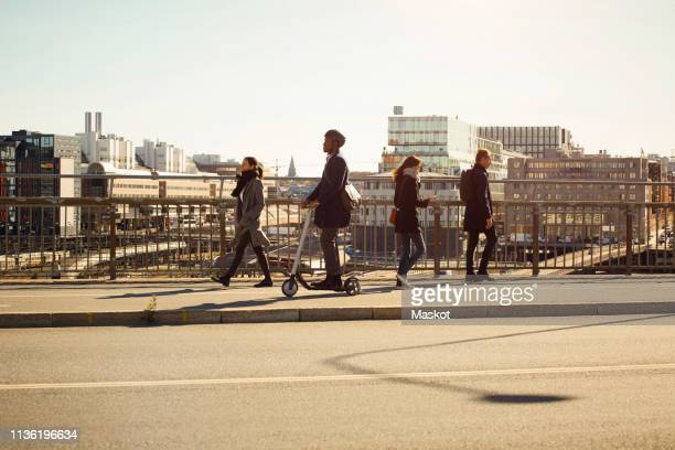 full length of men and women on bridge in city - electric scooter stock pictures, royalty-free photos & images
