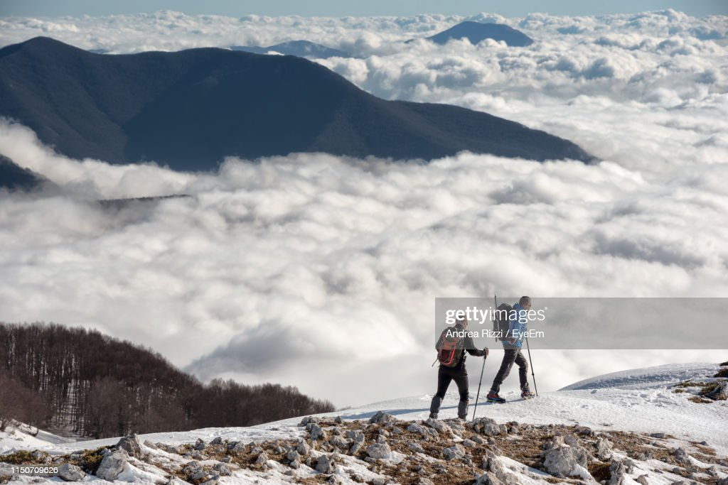 Full Length Of Men Walking On Snow Covered Land Against Cloudscape : Foto stock