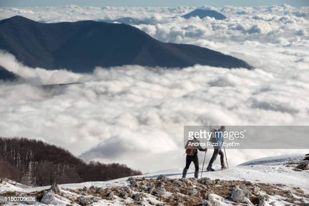 full length of men walking on snow covered land against cloudscape - andrea rizzi fotografías e imágenes de stock