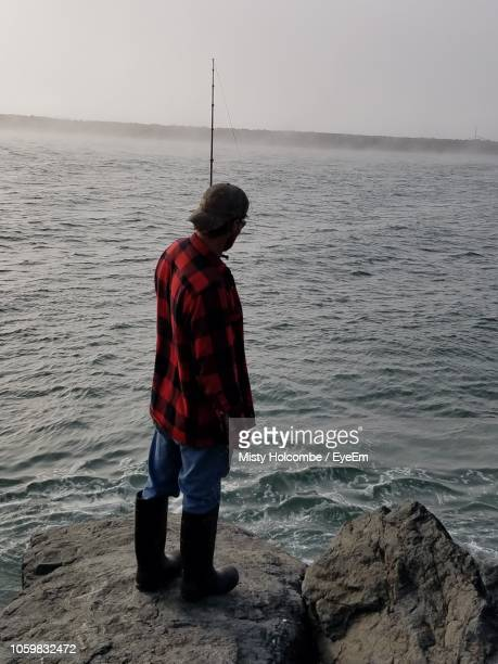 Full Length Of Mid Adult Man Standing On Rock In Sea Against Sky