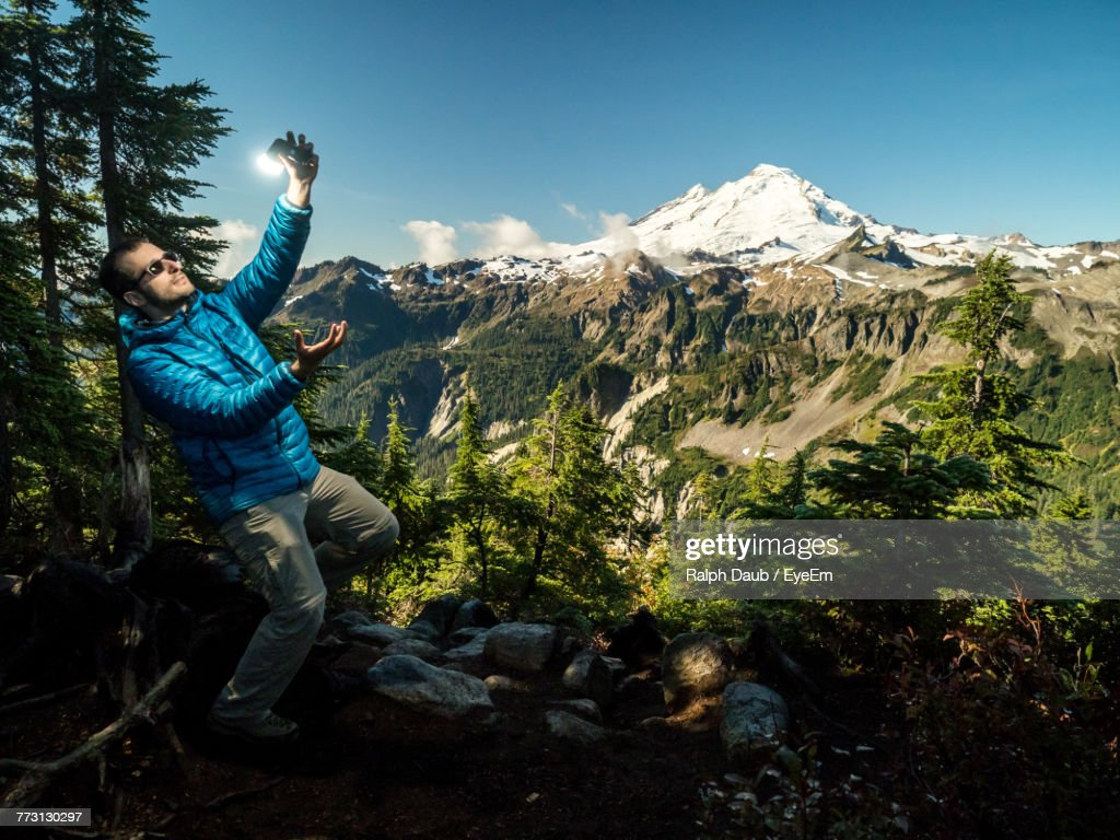 Full Length Of Mid Adult Man Talking Selfie While Standing On Mountain Against Sky : Photo