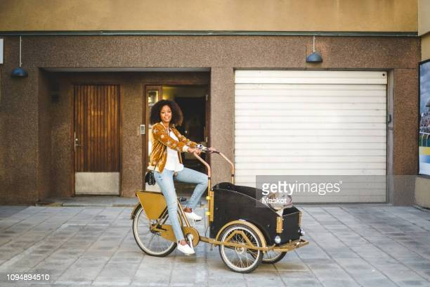 full length of mid adult woman riding bicycle cart with dog against building - trailer stock pictures, royalty-free photos & images