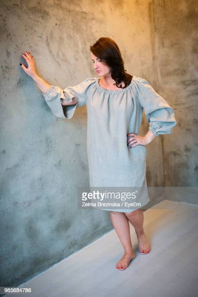 Full Length Of Mid Adult Woman Standing By Wall On Floor