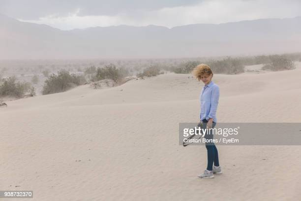 full length of mid adult woman standing on sand against sky - bortes stock pictures, royalty-free photos & images