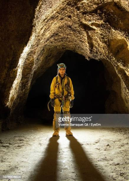full length of miner standing in cave - 鉱山労働者 ストックフォトと画像