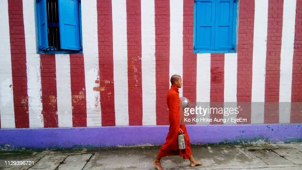 full length of monk walking against building - ko ko htike aung stock pictures, royalty-free photos & images