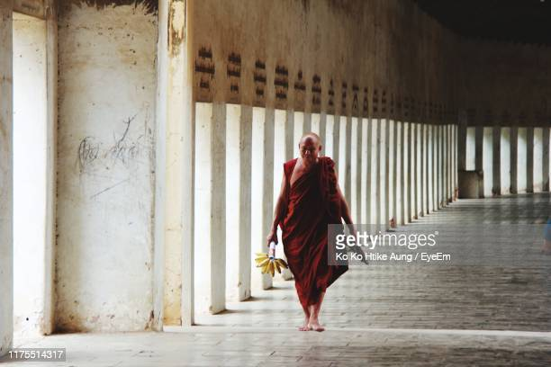 full length of monk walking in corridor - ko ko htike aung stock pictures, royalty-free photos & images