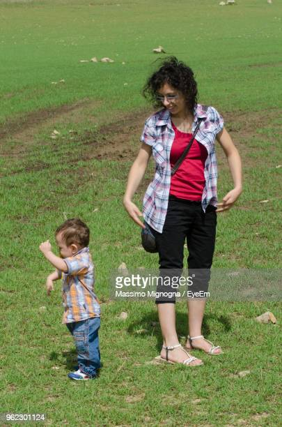 Full Length Of Mother And Son Standing On Field