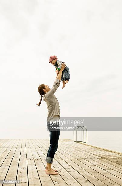 Full length of mother lifting baby girl while standing on pier against sky