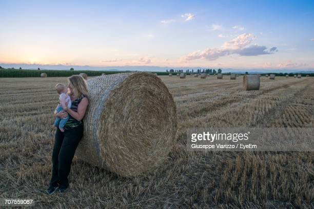 Full Length Of Mother With Baby Leaning On Hay Bale At Agricultural Field Against Sky During Sunset