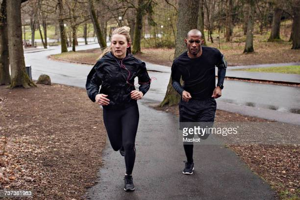 full length of multi-ethnic couple jogging on wet street - anstrengung stock-fotos und bilder