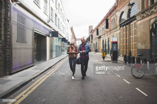 full length of multi-ethnic couple walking on city street - shoreditch stock photos and pictures