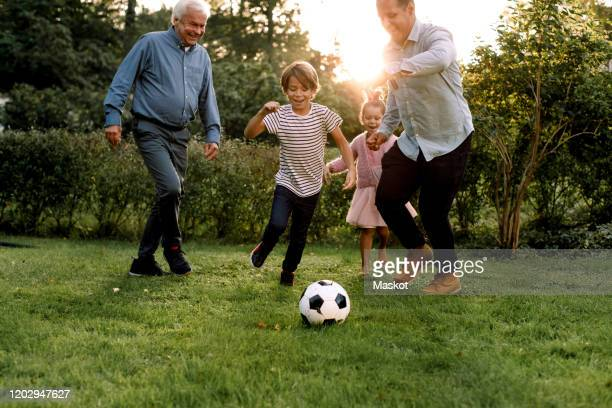 full length of multi-generation family playing soccer in backyard - football player photos et images de collection