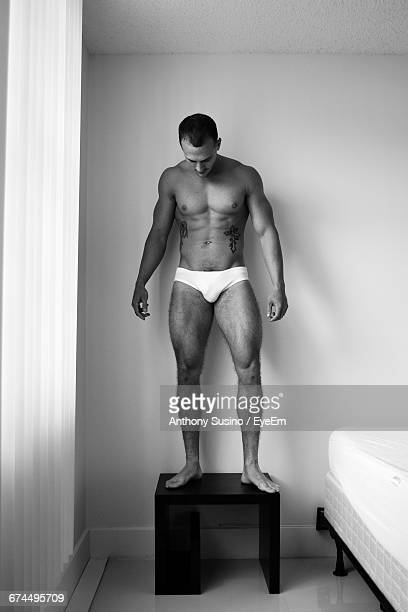 Full Length Of Muscular Man Standing On Night Table In Bedroom