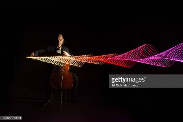 full length of musician playing cello by light painting against black background - lichtmalerei stock-fotos und bilder
