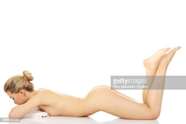 full length of naked seductive woman lying against white background - beautiful bare bottoms stock pictures, royalty-free photos & images