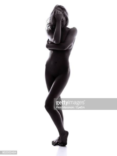 full length of naked woman standing against white background - mujer desnuda cuerpo entero fotografías e imágenes de stock