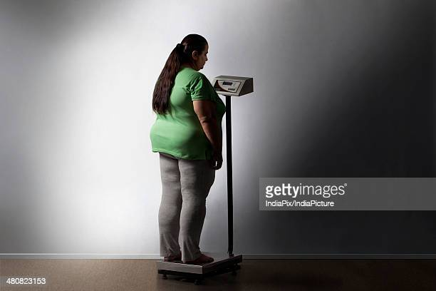 Full length of overweight woman measuring weight against wall at home