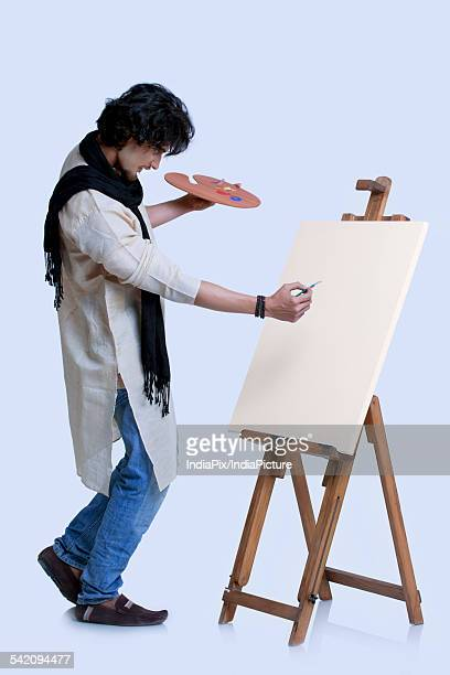 Full length of painter about to paint against colored background