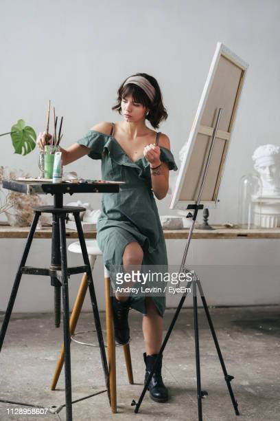 full length of painter sitting on stool by easel at art studio - easel stock pictures, royalty-free photos & images