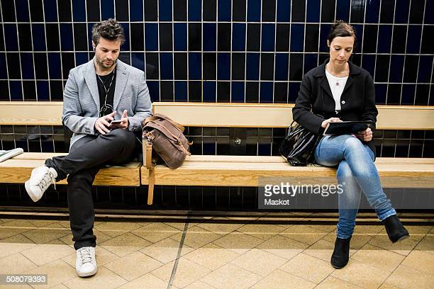 full length of people using technologies on bench at subway station - bank zitmeubels stockfoto's en -beelden