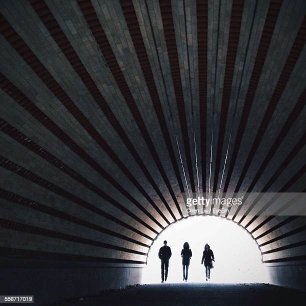full length of people walking in tunnel - light at the end of the tunnel stock pictures, royalty-free photos & images