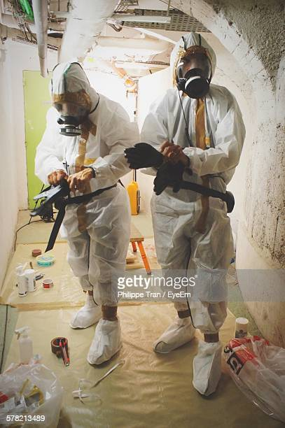 Full Length Of People With Gas Mask Wearing Protective Glove