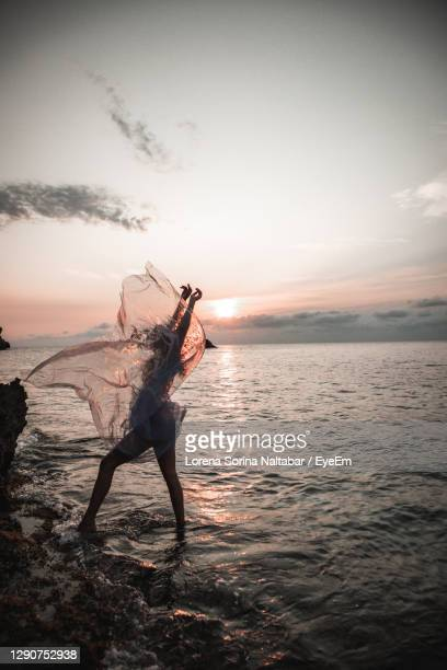 full length of person at beach against sky during sunset - lorena day stock pictures, royalty-free photos & images