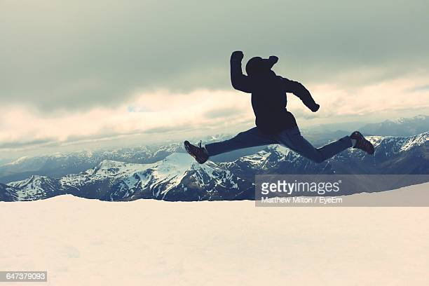 Full Length Of Person Jumping In Mid-Air On Snowcapped Mountain Against Cloudy Sky