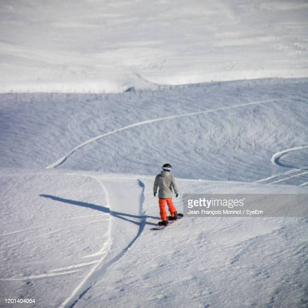 full length of person skiing on snowcapped mountain - carré composition photos et images de collection