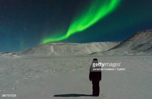 Full Length Of Person Standing On Snow Covered Field Against Aurora Borealis At Night