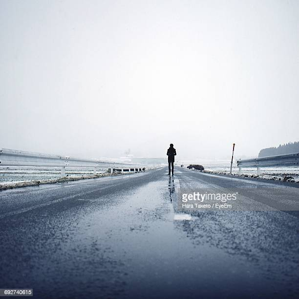 Full Length Of Person Standing On Wet Street Amidst Snow Covered Field Against Clear Sky