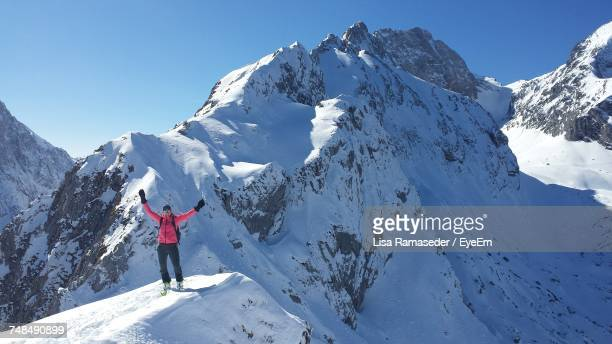 full length of person with arms raised standing on snowcapped mountains during sunny day - garmisch partenkirchen stock pictures, royalty-free photos & images