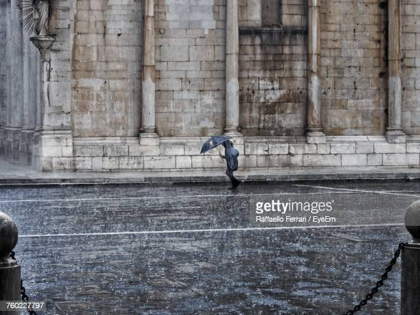 full length of person with umbrella walking on street during rainy season - torrential rain stock pictures, royalty-free photos & images