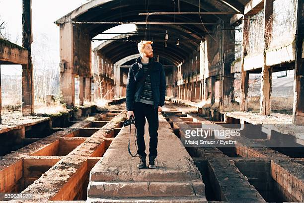 Full Length Of Photographer Standing In Abandoned Factory