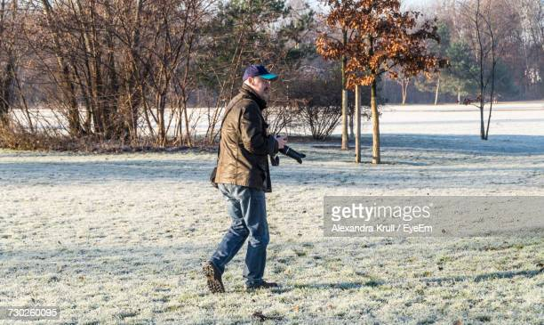 Full Length Of Photographer Walking On Field During Winter