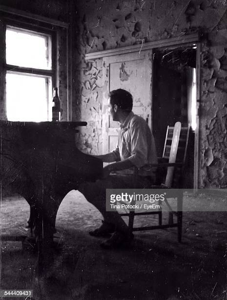 Full Length Of Pianist Playing Piano In Abandoned Home
