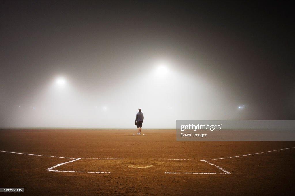 Full length of player standing on baseball field : Stock Photo