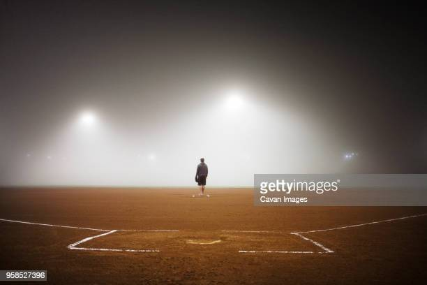 Full length of player standing on baseball field