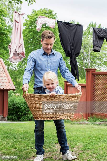 Full length of playful father carrying daughter in basket at yard