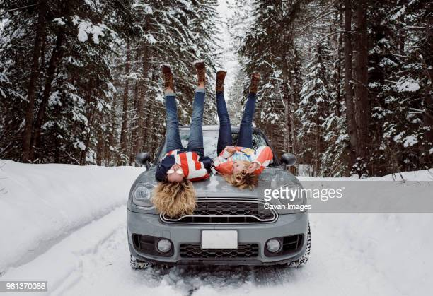 Full length of playful female friends lying on car's bonnet with feet up during winter