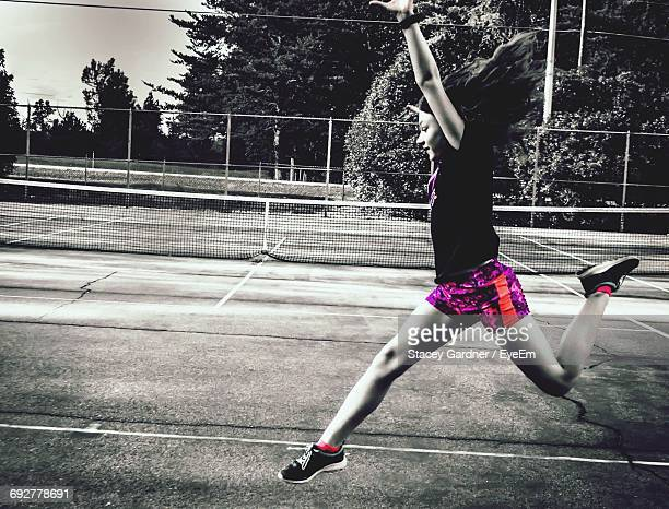 full length of playful girl jumping on playing field - isolated color stock pictures, royalty-free photos & images