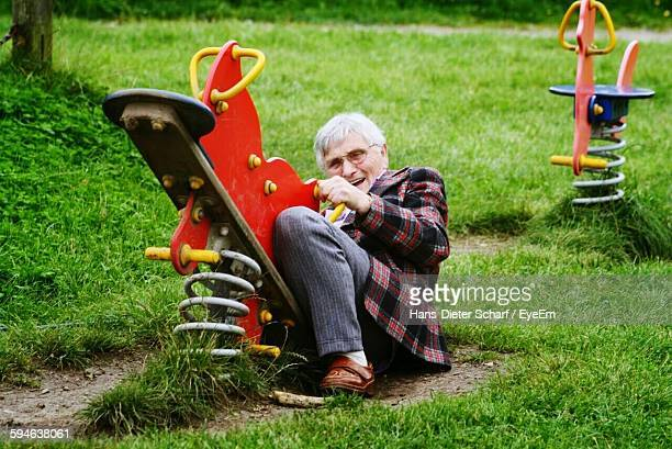 Full Length Of Playful Old Man Holding Spring Ride At Park