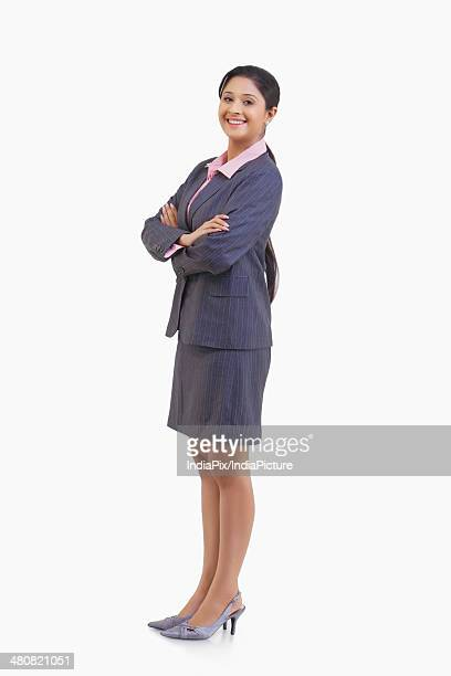 Full length of portrait young businesswoman standing arms crossed over white background