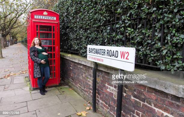 Full Length Of Pregnant Woman Leaning On Telephone Booth At Bayswater Road