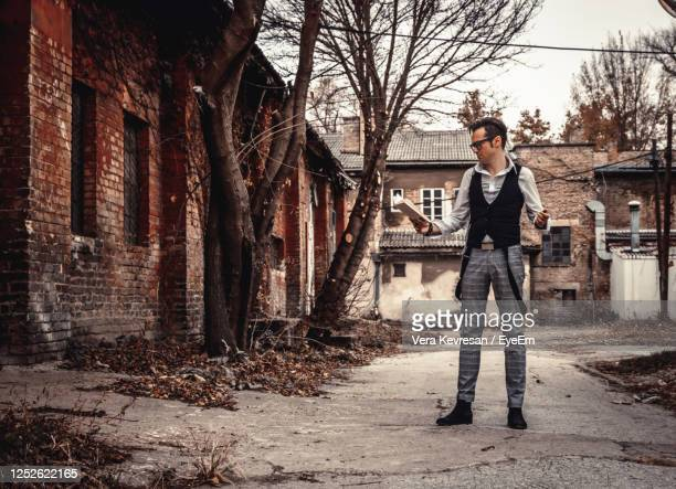 full length of retro-styled man standing outdoors and reading a book. - actress vera day stock pictures, royalty-free photos & images